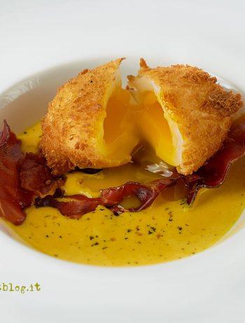 Uovo panko con doppia cottura, su crema di formaggio alla curcuma e speck croccante